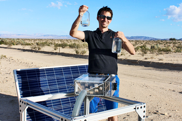 Prévot stands next to the water harvester and solar panel in the desert while holding up two bottles of water. He's grinning widely while wearing a black shirt and sunglasses.