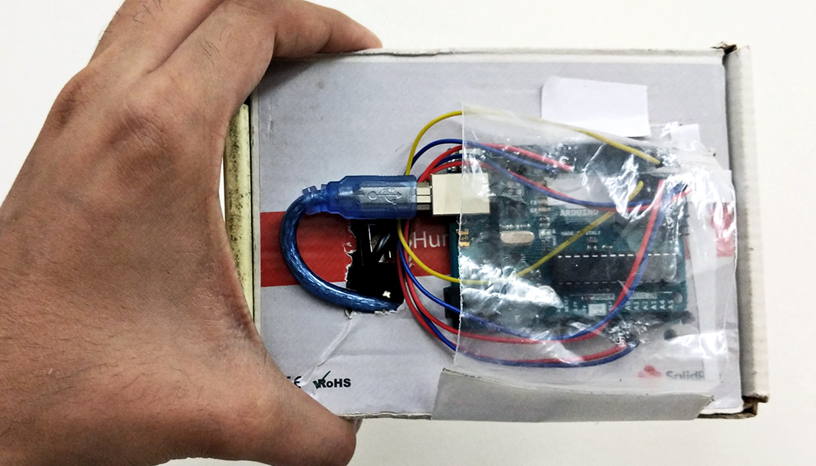 The device is a cardboard box with a USB cord coming out of it and into a chip covered in plastic