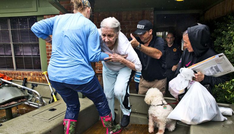 An older woman gets help to leave her house during a flood, as people help her into a boat and her dog watches