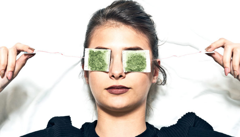 A young woman has green tea bags over her eyes as she lies in bed