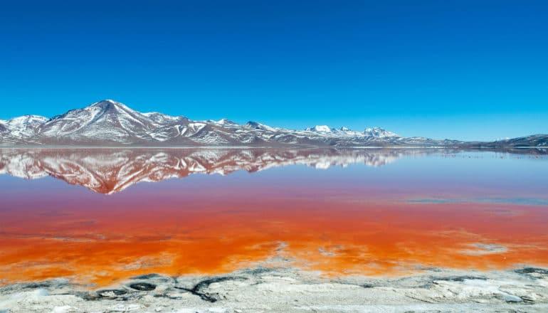 gray mountains behind bright orange shallow water