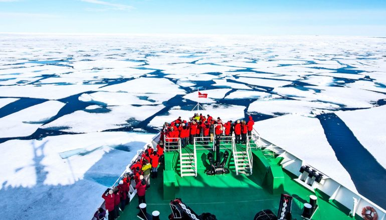 a green ship with passengers in red jackets moves through Arctic sea ice, which is broken into large sheets with the ocean showing in between