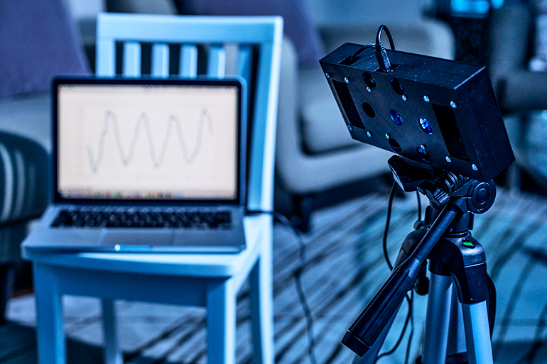In a dark room, the smart speaker is connected to a laptop that shows a waveform