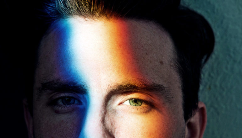 A man's face with colored light shining on it