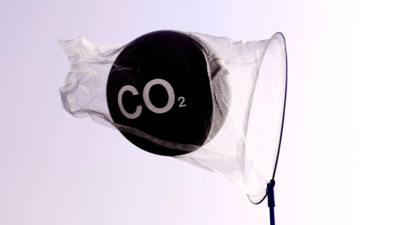 "A net holds a black ball labeled ""CO2"" against a white sky"