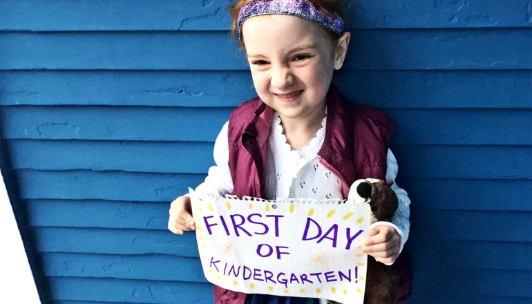 """A kindergartener holds up a sign that says """"First day of kindergarten"""" as she smiles and stands in front of a blue wall while posing for a picture"""