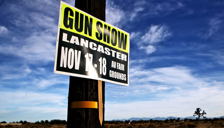 A sign on a telephone pole advertises for a gun show