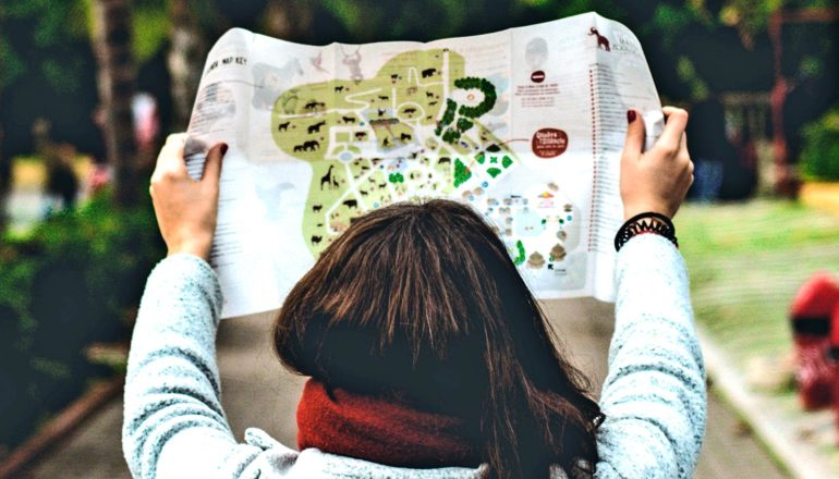 A young woman holds up a map with a path in the background