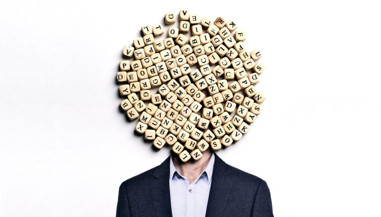 A man in a suit has letter tiles covering his face