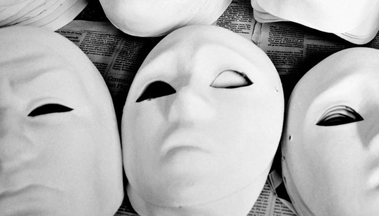 A set of unpainted masks sit on a newspaper
