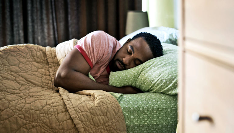 A man in a red t-shirt sleeps on green sheets