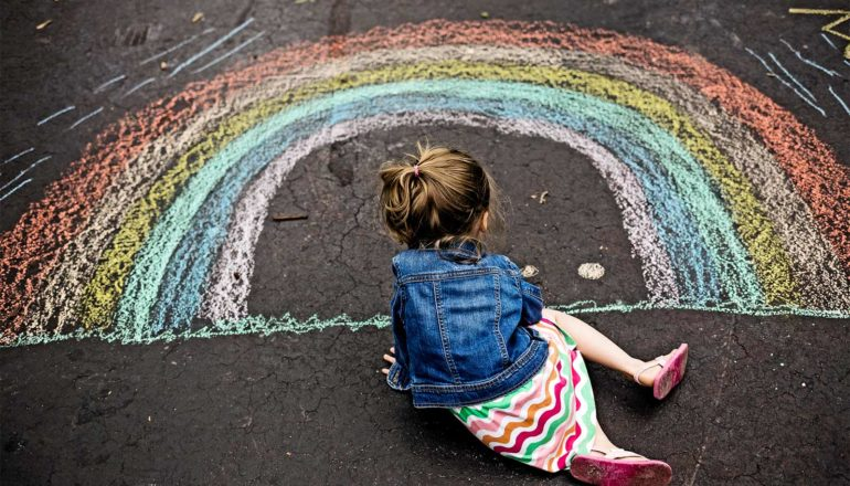 a young girl sits on asphalt drawing a rainbow with chalk