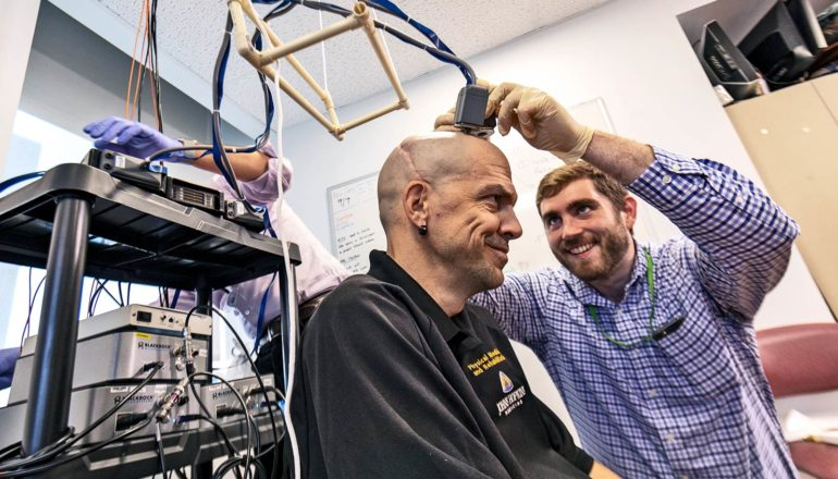 A researcher attaches electrodes to Chmielewski's head as they both smile