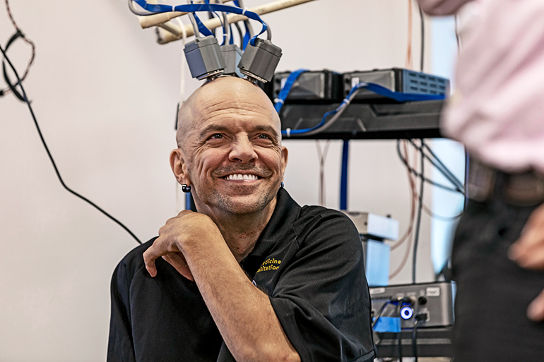 Chmielewski smiles widely with electrodes attached to his head and electronic equipment behind him