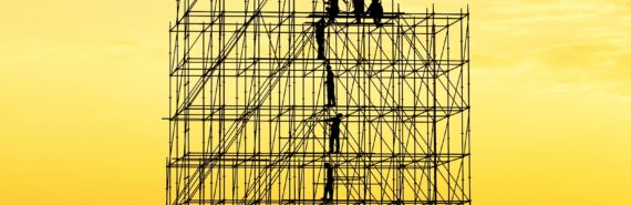 Construction workers appear tiny while standing on a large scaffold in silhouette against a yellow-orange sky
