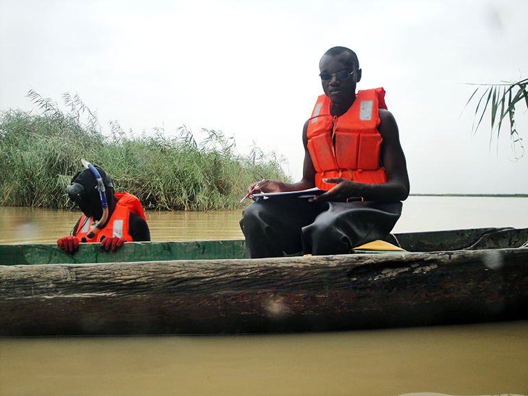 One team member in an orange life jacket sits in the boat while one stands in the water with a snorkel and life jacket on