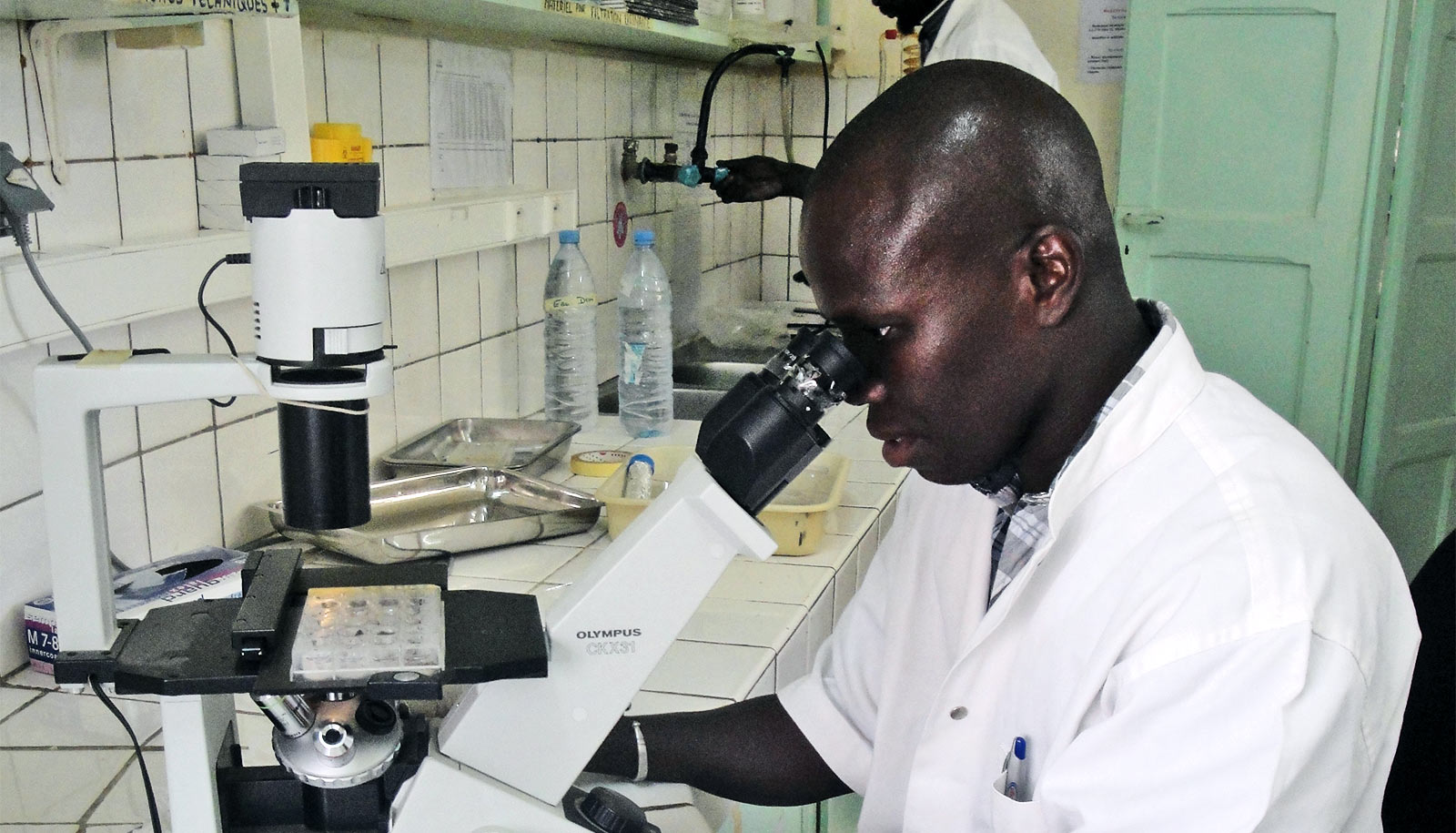 Senghor looks into a microscope while wearing a white lab coat