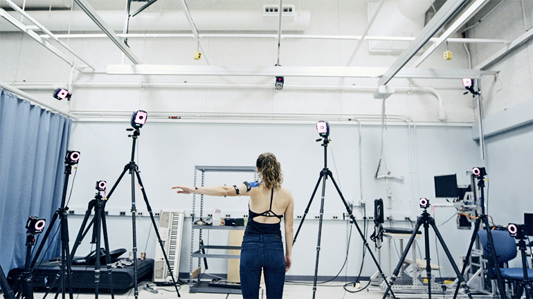 A researcher wearing the patch lifts her arm as cameras surrounding her monitor her movement