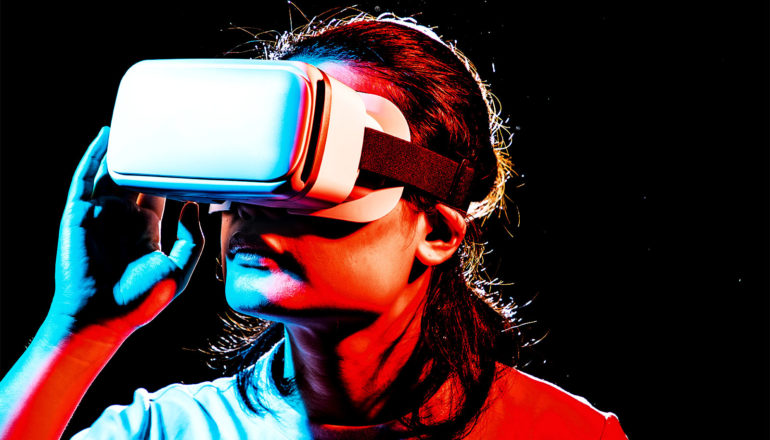 A person wears a virtual reality headset while covered in blue and red light against a black background