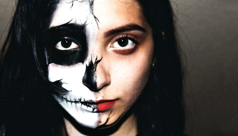 A young woman has half her face painted with black and white skull facepaint