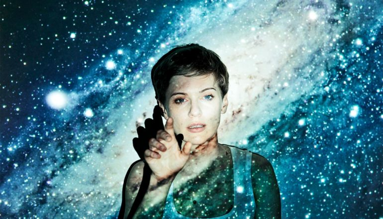 A young woman looks curious as she reaches her hand out while an image of space is projected on her face