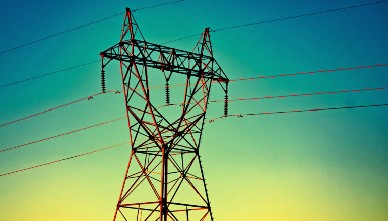 An electrical tower with wires coming out of it stands against a sunset-like background with blue at the top of the frame and yellow at the bottom
