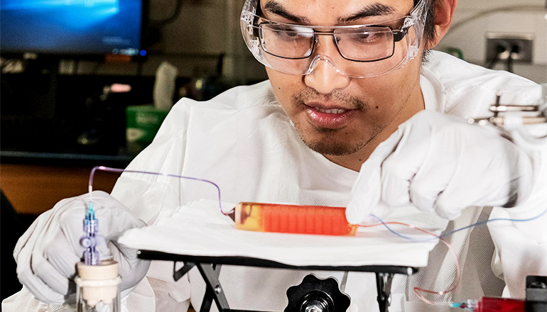 A researcher in white coat and gloves looks down at the small 3D-printed device, which could fit in his palm