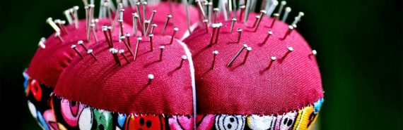 A red pin cushion with many pins in it