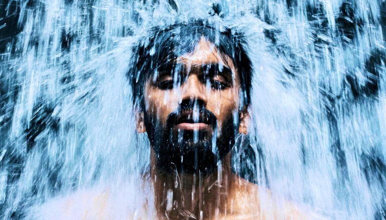 A man closes his eyes as a waterfall pours down on his head