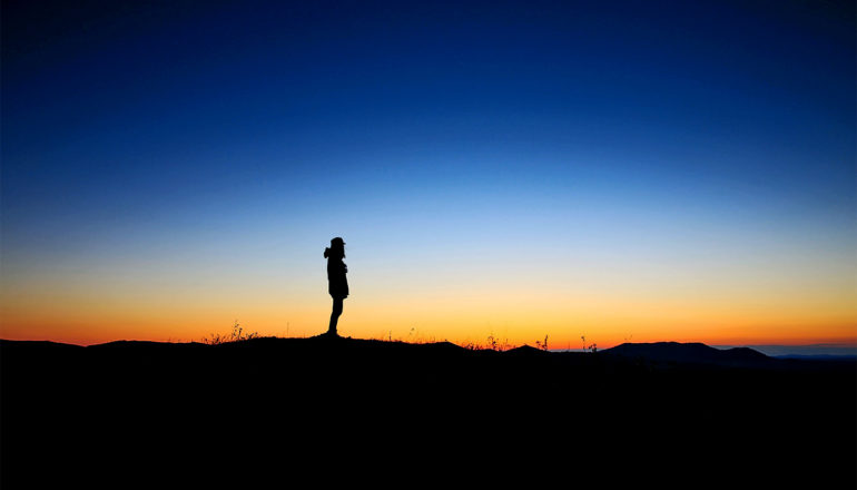 A person in silhouette stands on dark ground with a sunrise in the background