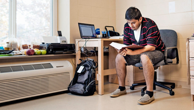 person reads book at desk in dorm room