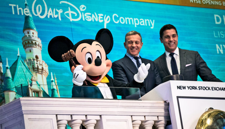 A person playing Mickey Mouse holds a gavel at the New York Stock Exchange, shrugging for humor, next to the Disney CEO