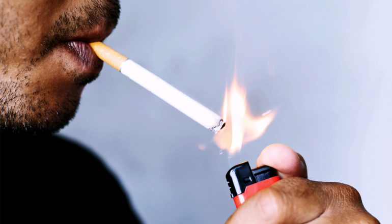 A man lights a cigarette against blue background, with only his mouth, the cigarette, and the lighter in his hand visible