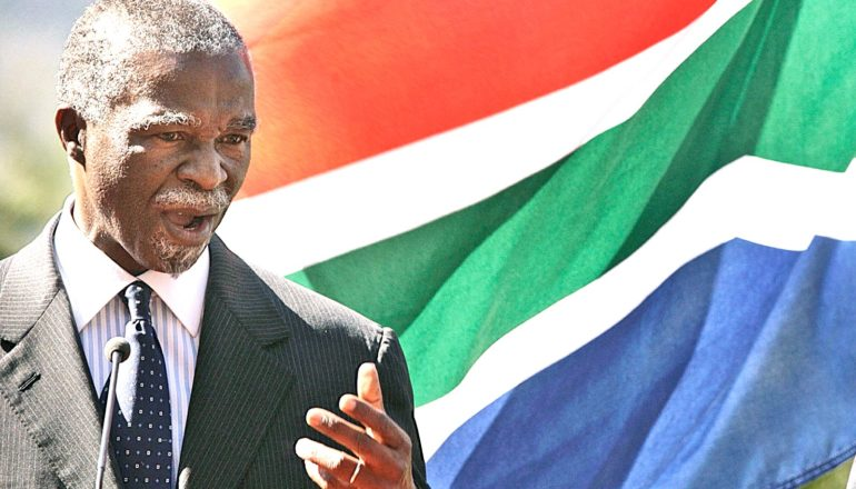 Former South African President Thabo Mbeki speaks while standing in front of a waving South African flag