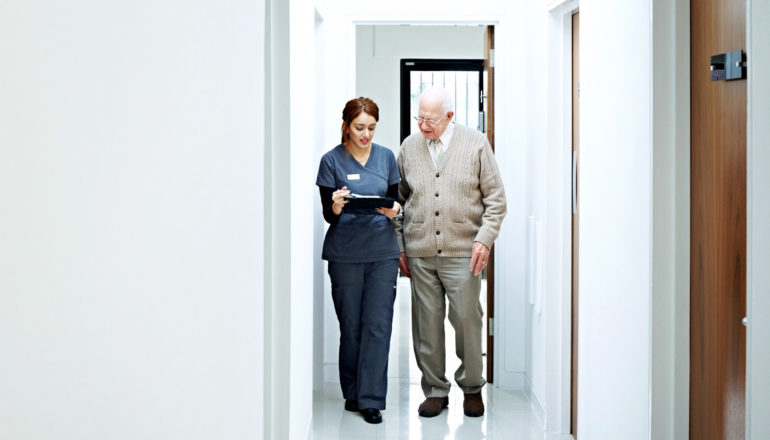 person in scrubs with clipboard walks in hallway with elderly patient