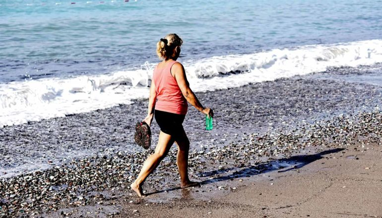 An older woman in a pink top holds her shoes and a waterbottle as she walks on a rocky beach, with a small wave crashing behind her