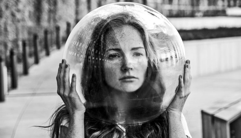 A woman holds a clear, bubble-like helmet over her head in black and white