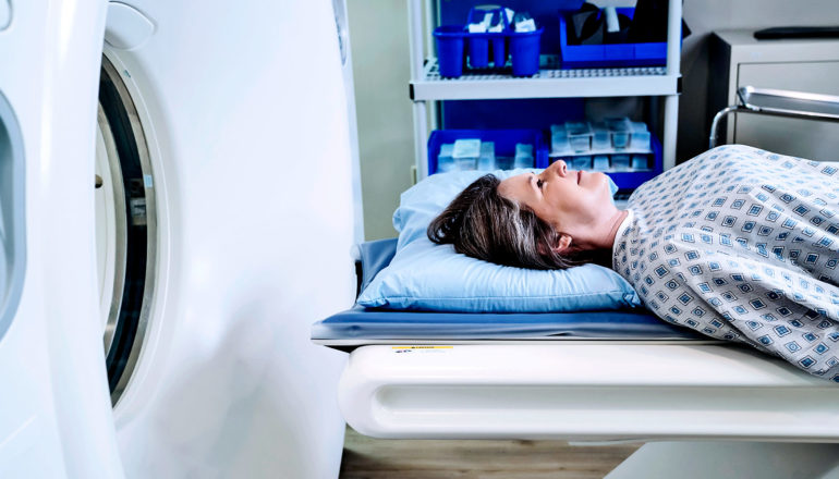 A woman waits for an MRI while lying on an an exam table