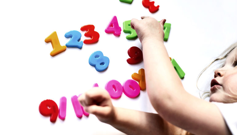 A child touches brightly colored plastic numbers on a white surface