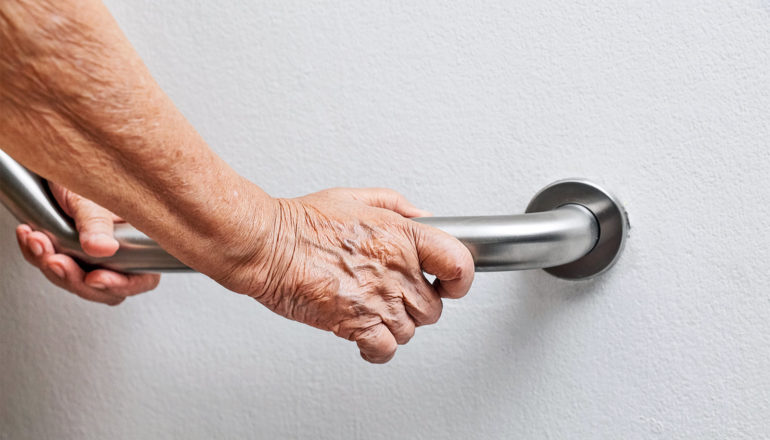 An older person holds on to a metal hand rail on a white wall