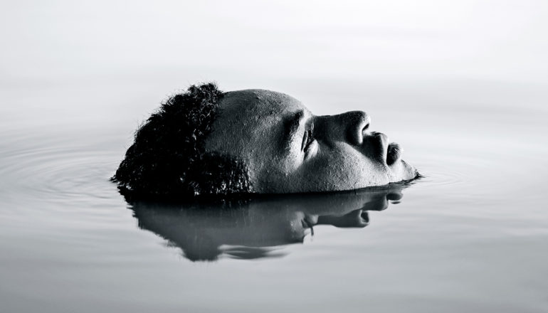 A man is submerged in water with just his face showing, which the water is also reflecting
