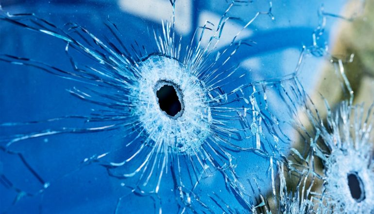 2 bullet holes in glass reflecting blue light