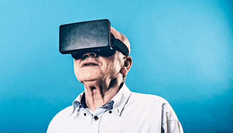 An older man wears a black virtual reality headset against a bright blue background