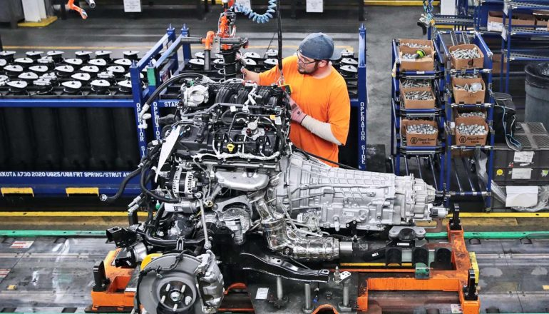 auto worker with car engine on plant floor