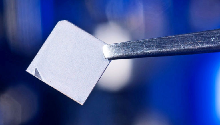 A pair of tweezers holds a small square of the new film.