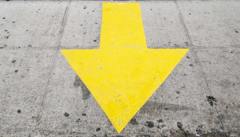 """A yellow arrow points down as if to say """"here"""" on some gray concrete"""