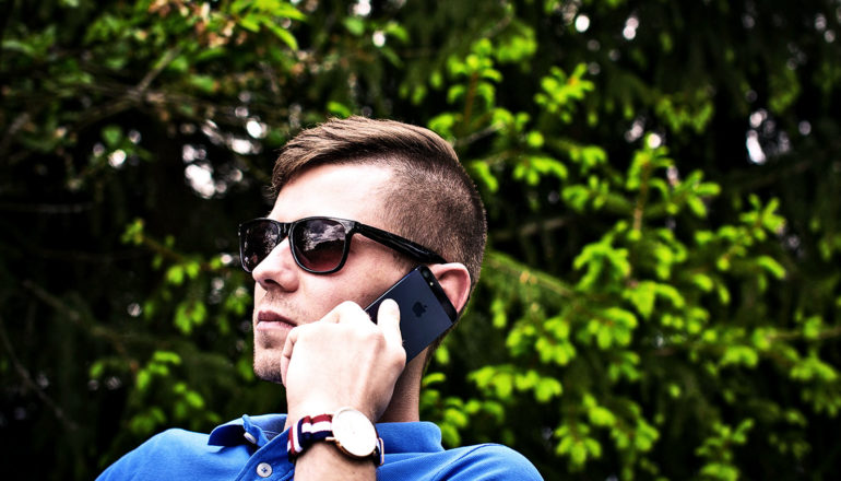 A man in a blue polo shirt and sunglasses talks on a cell phone against a background of green leaves