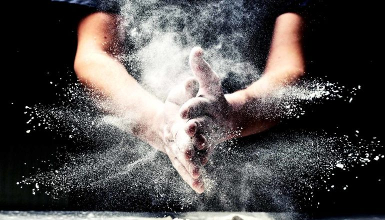 A person claps their flour-covered hands together, sending flour flying in every direction, all against a dark background