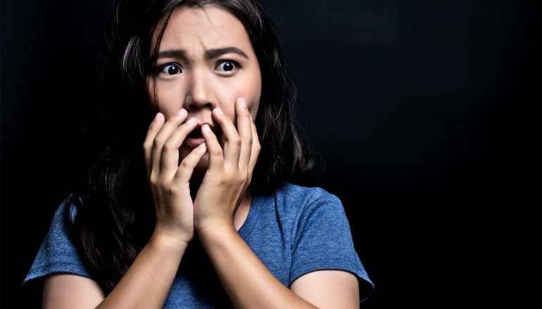 A woman in a blue t-shirt looks horrified against a black background