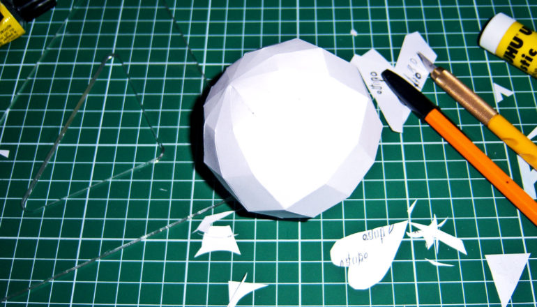 A kirigami sphere sits on a green work surface with pens, rulers, and scraps of paper around it